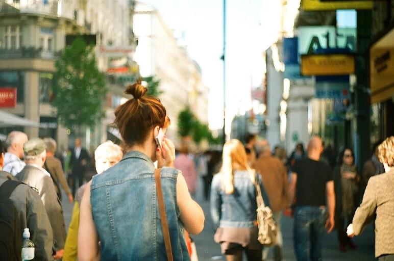 trabalho externo - Mulher falando ao telefone em uma rua movimentada